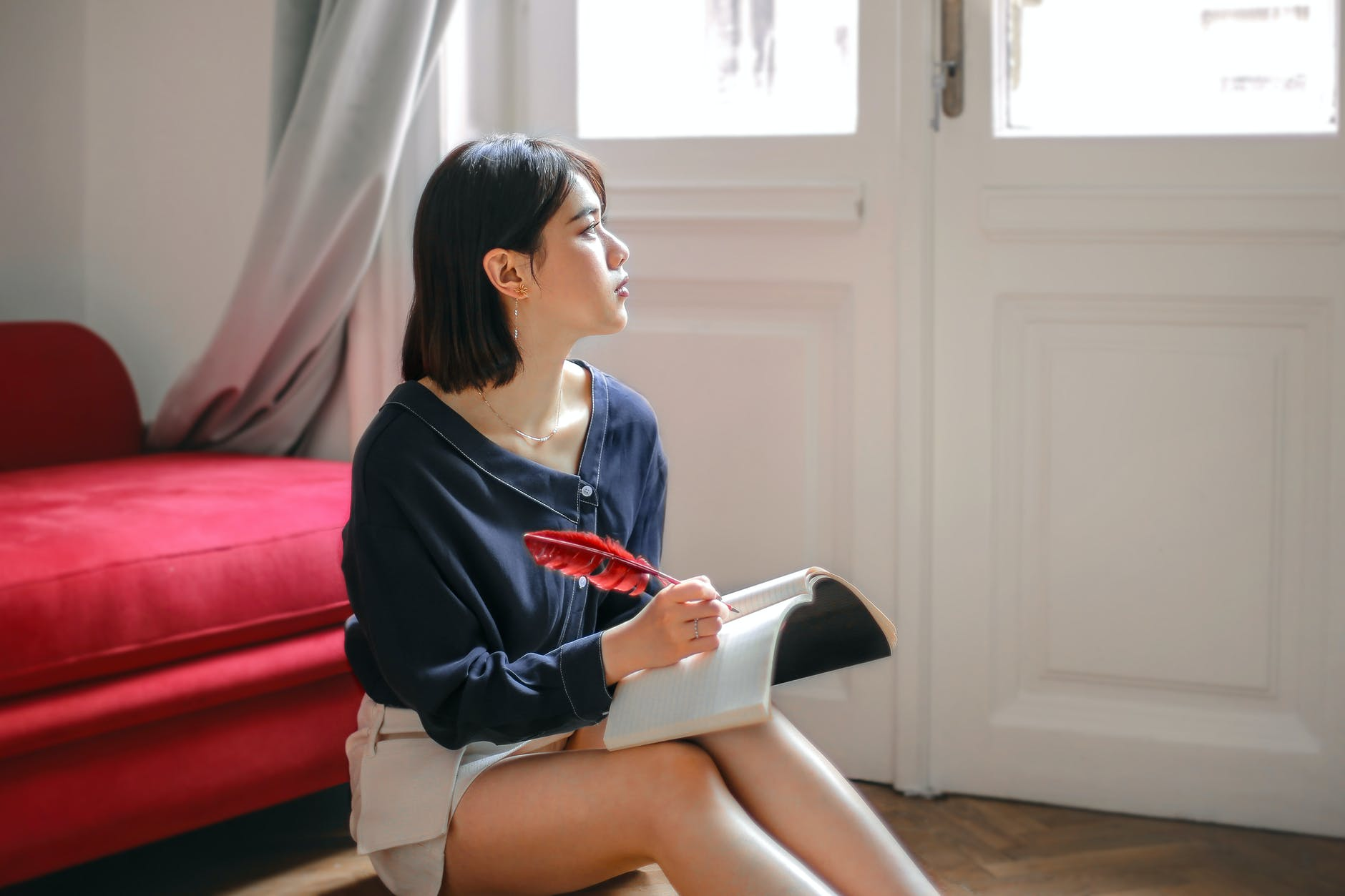 thoughtful woman writing in notebook at home