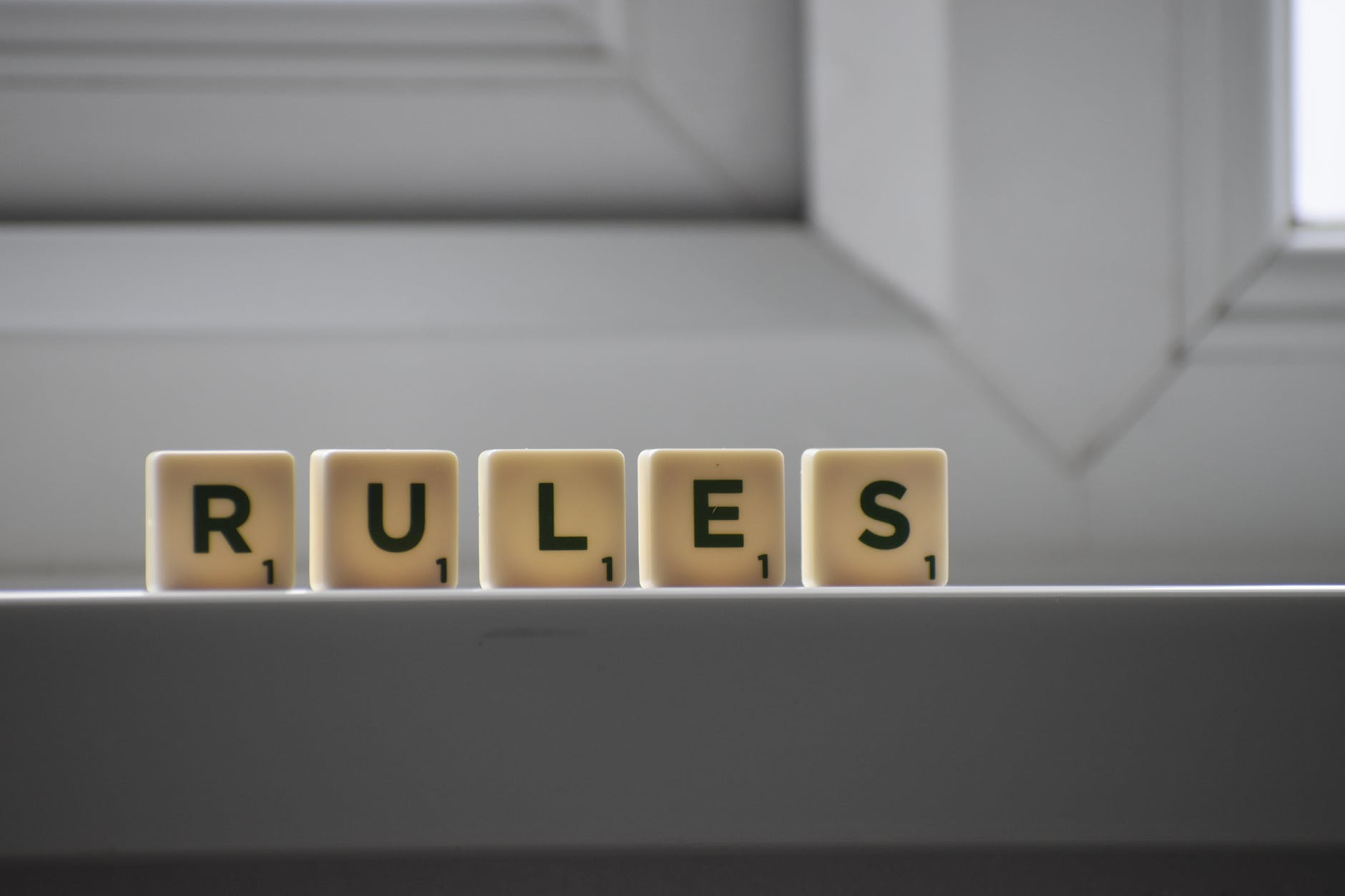 similar cubes with rules inscription on windowsill in building