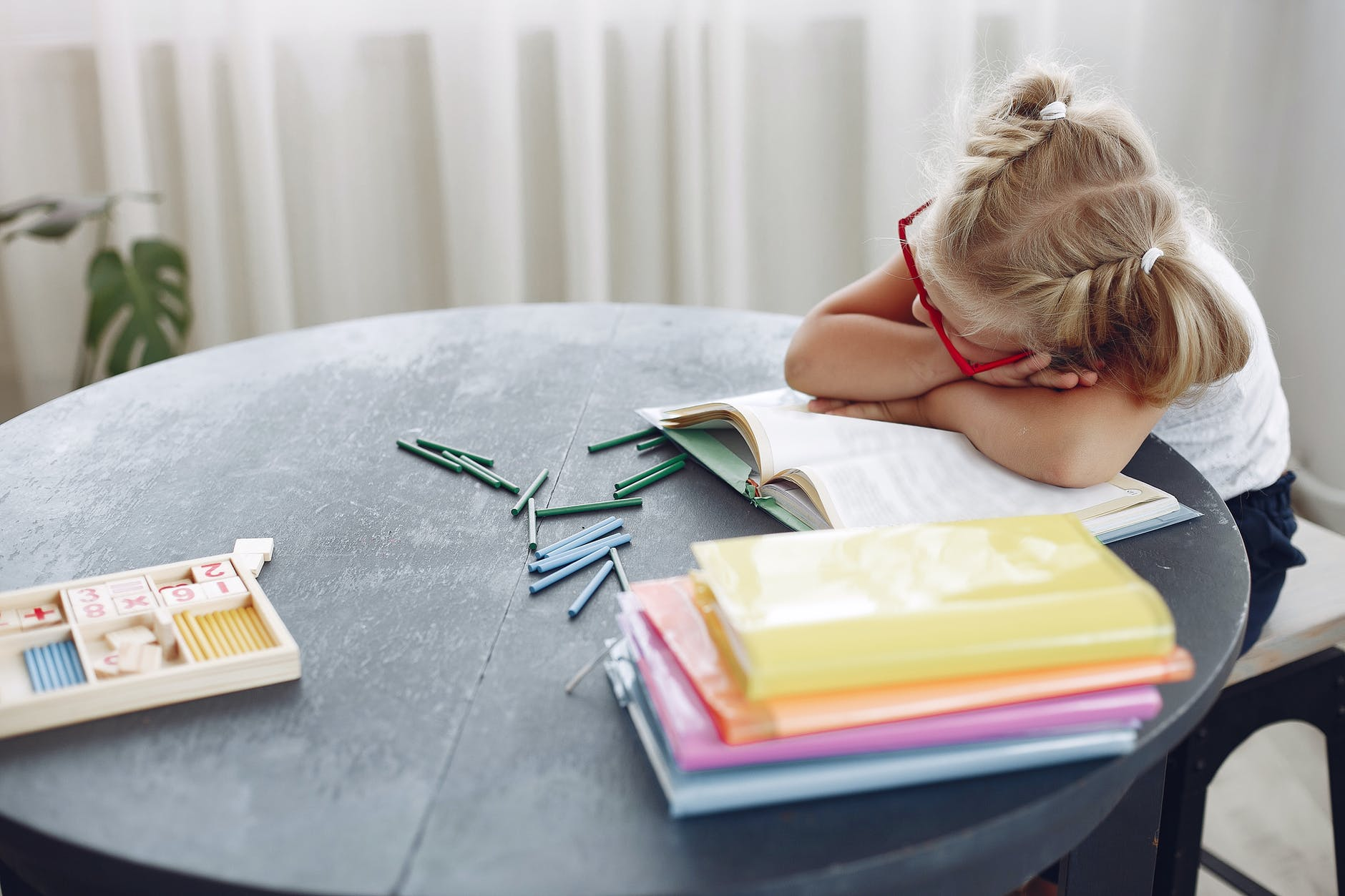 tired little girl sleeping on book at home