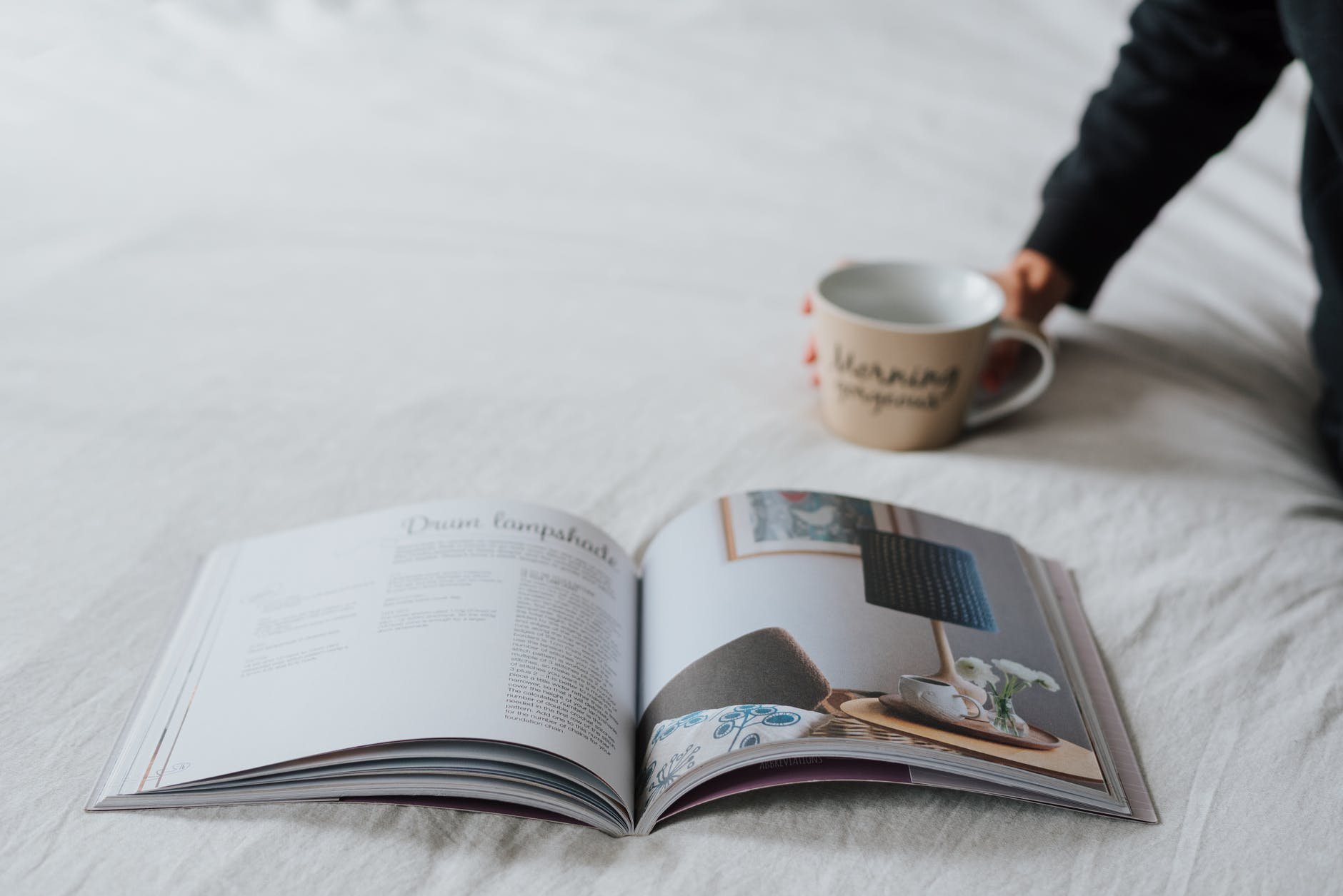 crop faceless person resting on bed with magazine and coffee
