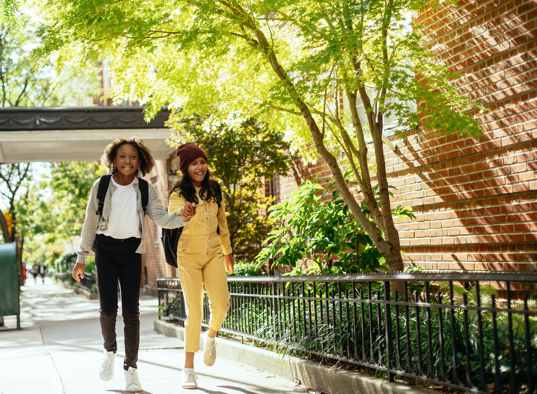happy diverse girls smiling on street with green tree
