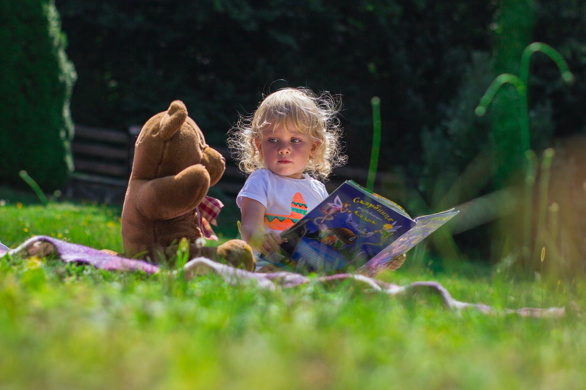 girl sitting beside a teddy bear