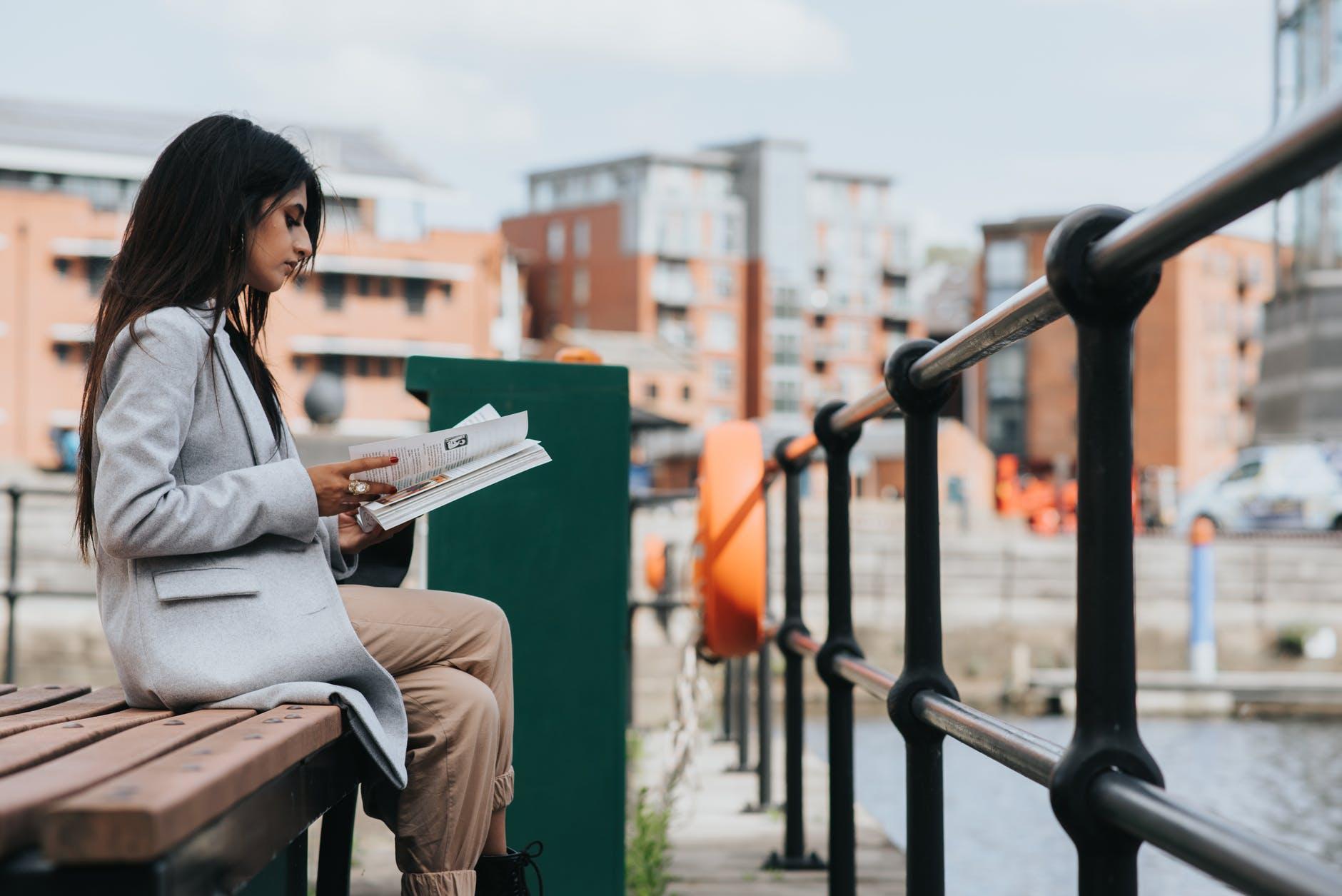 serious ethnic stylish lady reading magazine on bench
