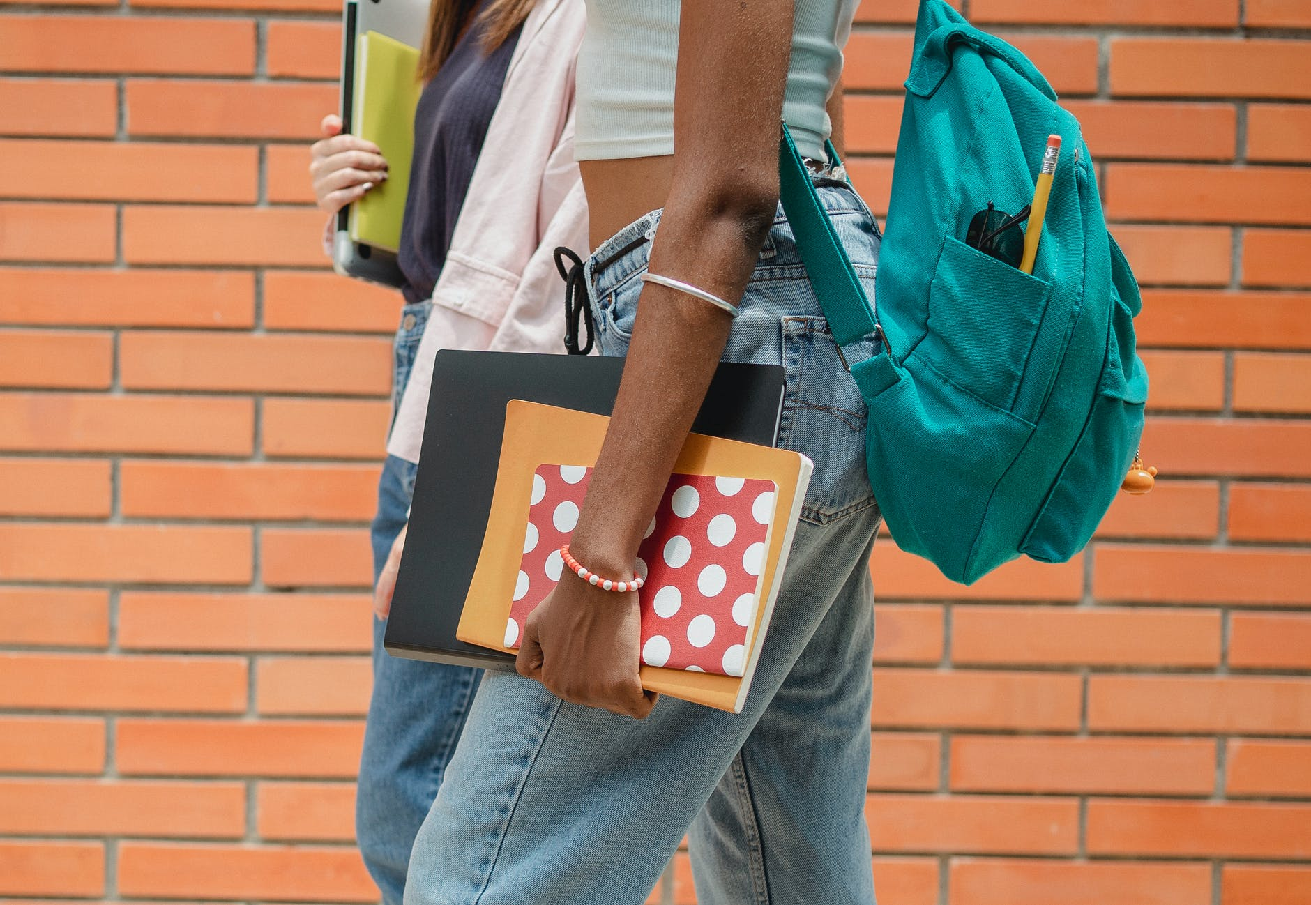 crop diverse multiethnic students with textbooks walking on sidewalk together