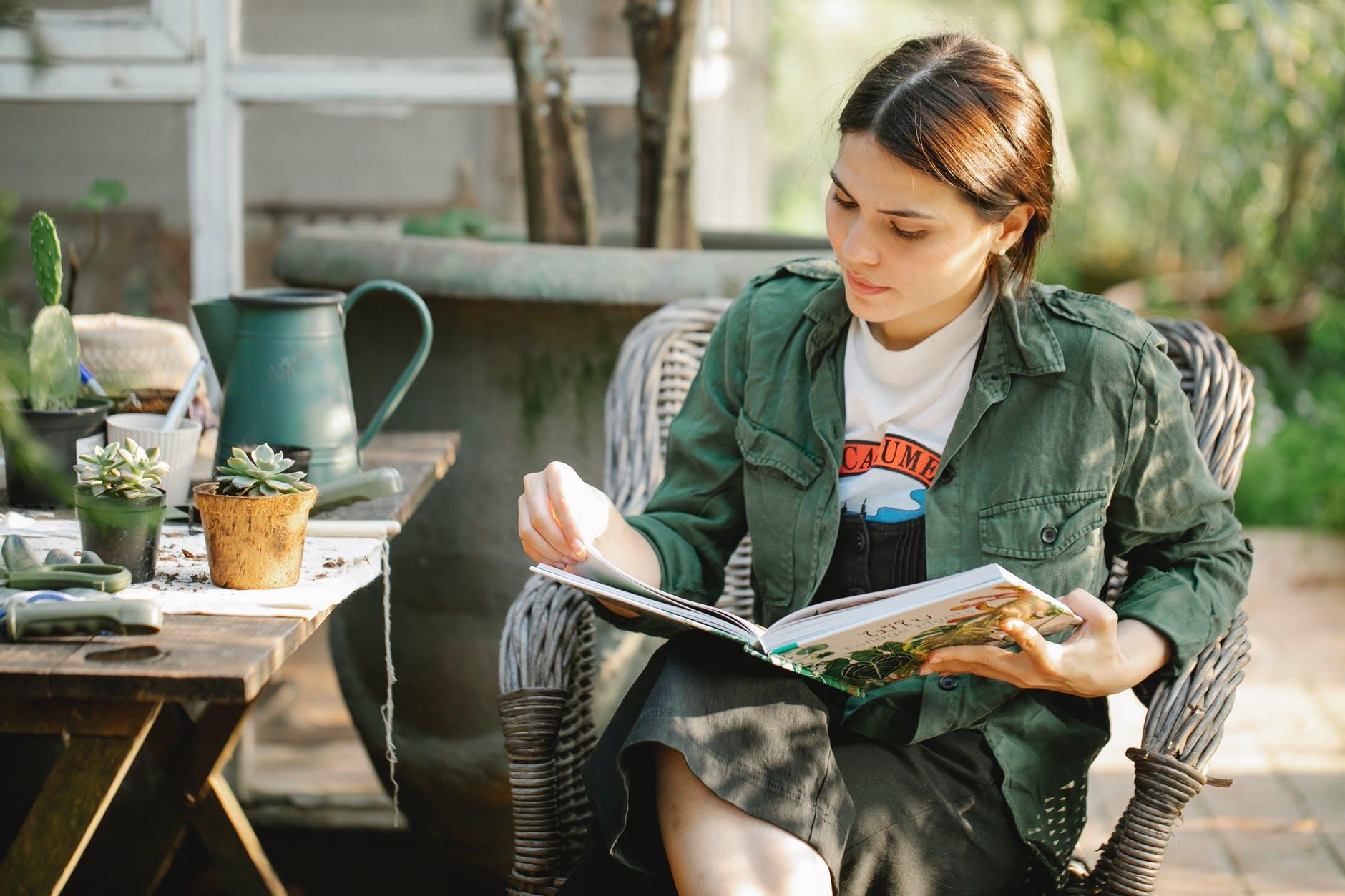 gardener reading book in armchair near plants in pots